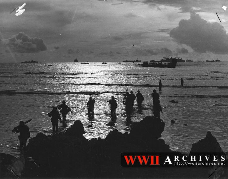 Battle of Tinian, July 24, 1944 - August 1, 1944. World War II Photograph: From a Coast Guard-manned landing craft, American invaders wade through a golden, shallow surf to hit the beach of Tinian Island near Guam in the Marianas.  In this striking sunrise silhouette, units of a mighty task force stand on the horizon -- Navy warships, transports and LSTs.  In closer, smaller invasion craft are halted by shallow water about 100 yards off shore.