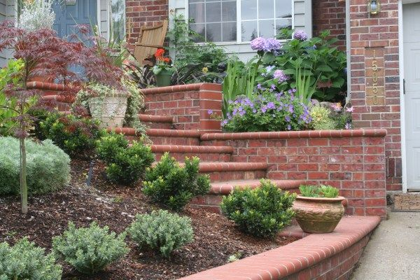 """""""Carry the materials of your home's exterior through to your front yard landscaping for a seamless transition between the two. Brick retaining walls, stone steps, even wood planters – all of these things can enhance the prominence of both your home and yard"""""""