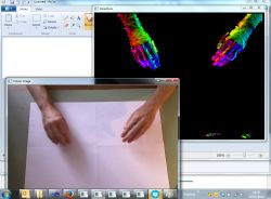 A screen snapshot of two application windows showing the same pair of hands, one in RGB colour, the other a colourized visualisation of the hands' IR signal.