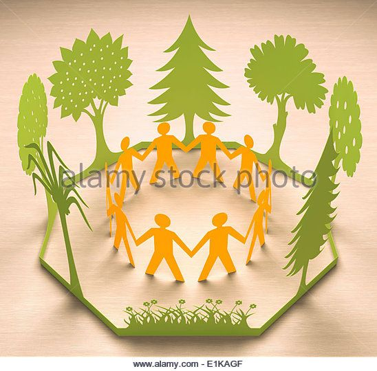 Paper chain of people holding hands with trees studio shot. - Stock Image
