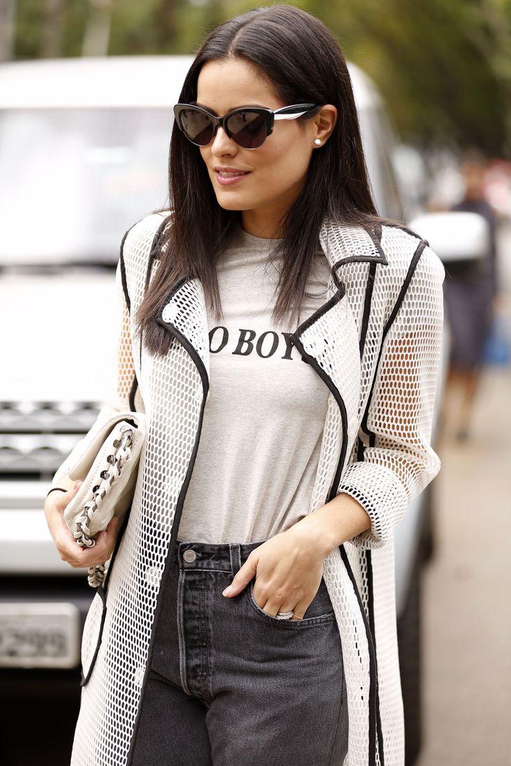 Confira o look de street style de Mariah Bernardes durante o SPFW. Camiseta Hello Boys com mom jeans, bota prateada YSL e, pra completar, sobretudo branco meio transparente.