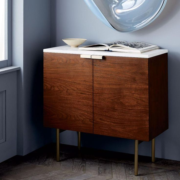 A sleek marble top and slim metal legs add a touch of refinement to our Delphine Console's espresso-finished body. Two cabinets offer a stylish storage solution for books, linens or other odds-and-ends.