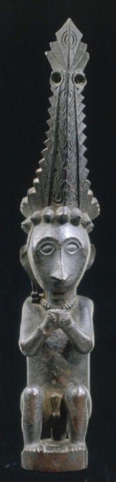 Nias Monoxyle, cette effigie représente un personnage masculin de haut rang assis sur un siège. Sculptée dans un bois dur puis recouvert d'une patine devenue croûteuse, elle reprend les canons en vigueur chez les nobles de Nias. Paré de ses atours, cet ancêtre porte la couronne aux bords dentelés et à décors de fougères <ni'owöli wöli> exécutée avec un méticuleux souci du détail qui s'élève au-dessus d'un bandeau à cabochons en pointe de diamant. La forme et le décor de la couronne…