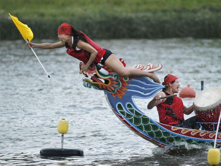 The boat captain grabs her finish line flag during a traditional Chinese Dragon Boat race in Taipei, Taiwan. Dragon boat races are in remembrance of Chu Yuan, an ancient Chinese scholar-statesman, who drowned in 277 B.C. while denouncing government corruption.  Wally Santana, AP