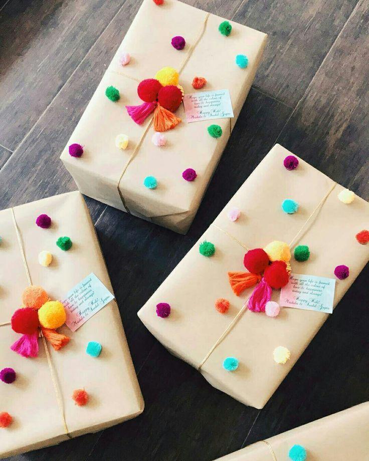 Embrulhos de presentes com papel pardo e pompons c…