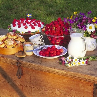 Midsummer fika with strawberry cake, cinnamon rolls and fresh strawberries with milk.