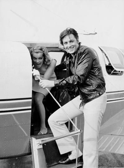 """Alain Delon, after coming welcome Romy Schneider, at the airport of Nice, French Riviera, on August 12, 1968, leave both for Saint-Tropez for shooting """"La Piscine"""" (""""The Swimming pool"""") by Jacques Deray, in Ramatuelle and Saint-Tropez. Photo by Jean-Pierre Bonnotte / Gamma-Rapho."""