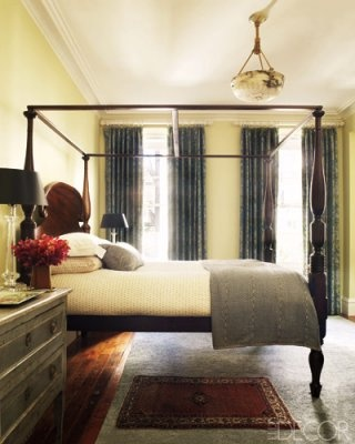 An antique chest of drawers and crystal lamps by Visual Comfort  Co. sit beside the antique bed, which is dressed in bedding by John Robshaw Textiles and Pratesi; the walls are painted in Citron by Farrow  Ball