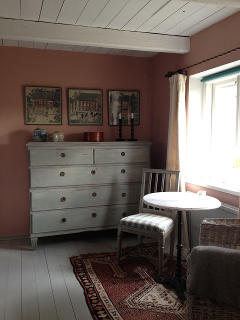 Rusty colored cottage walls + cream chest of drawers