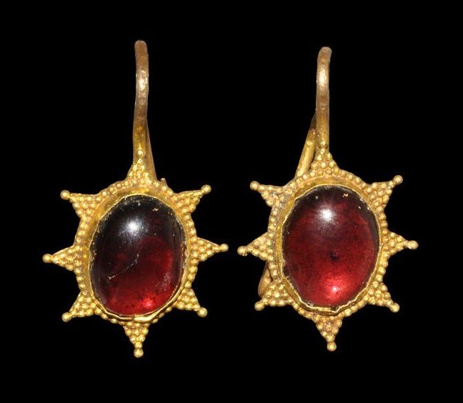 Byzantine Gold and Garnet Earrings 5th-8th century AD . A pair of gold earrings each with suspension loop and elliptical plaque, cabochon garnet and granule starburst surrounding