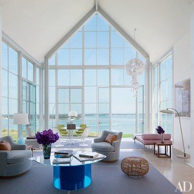 Knoll CEO Andrew Cogan and his wife, Lori Finkel, commissioned architect Michael Haverland and decorator Philip Galanes to expand their house on New York's Shelter Island. In the living room, 1950s swivel chairs by Edward Wormley for Dunbar are grouped with a cocktail table by Nicola L. and a '60s Franco Albini rattan ottoman | archdigest.com