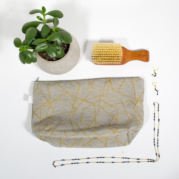 """Travel kit - Laser  Makeup bag with waterproof interior, perfect for all your cosmetics, flat iron and all your toiletries during your small or big trip  Exterior fabric; Laser grey and gold embroidery (55% Polyester / 45% Coton) Waterproof nylon interior  Dimension: 12-1/2 """" x 7-1/2""""h Base 4"""" large Zipper 12"""""""