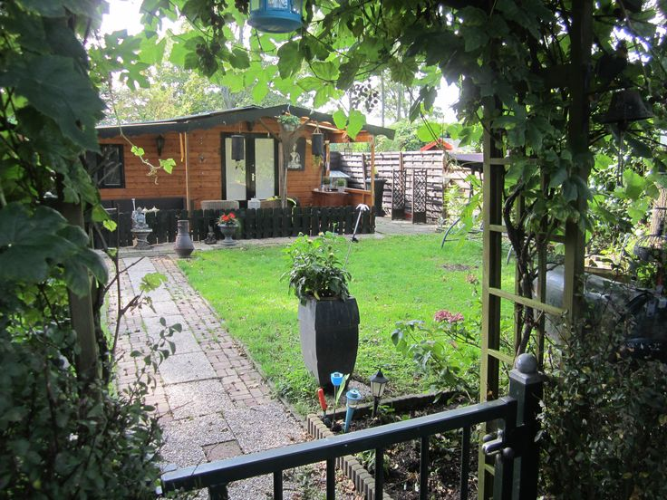 Houten gelakt tuinhuisje met zwarte randen en kleine overkapping!