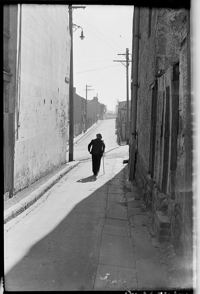 Old age pensioner in Surry Hills alley with stick. Sydney 1949