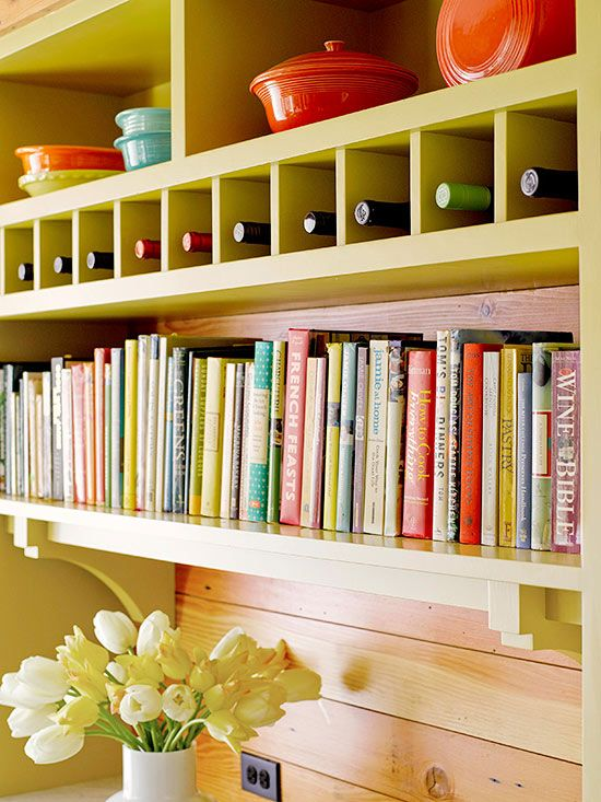 Oh, what to do with all those cookbooks? This bright bookshelf/storage wall solves that problem with style. Simple cubbies above the books store single bottles of wine, and colorful baking and serving dishes are displayed on the shelves above.