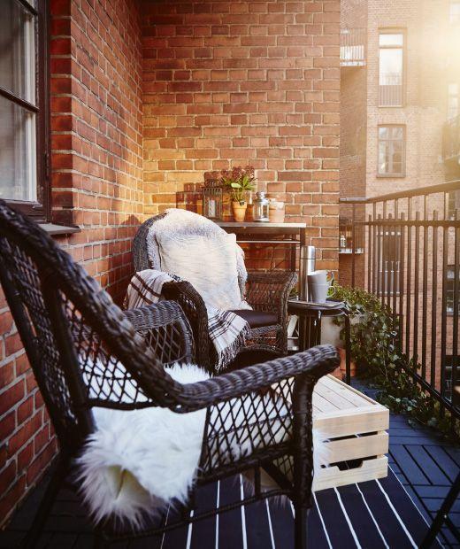 Un balcó preparat per a la primavera primerenca, amb cadires cobertes amb pell d'ovella, plantes en testos en un carret i tasses de cafè sobre una cadira.