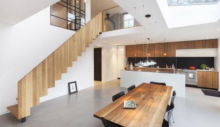 Moderne eetkeuken met vide. Door het daklicht boven de eettafel en de vide valt er veel licht de woonkeuken in. Ontwerp door Bloem en Lemstra Architecten uit Amsterdam.