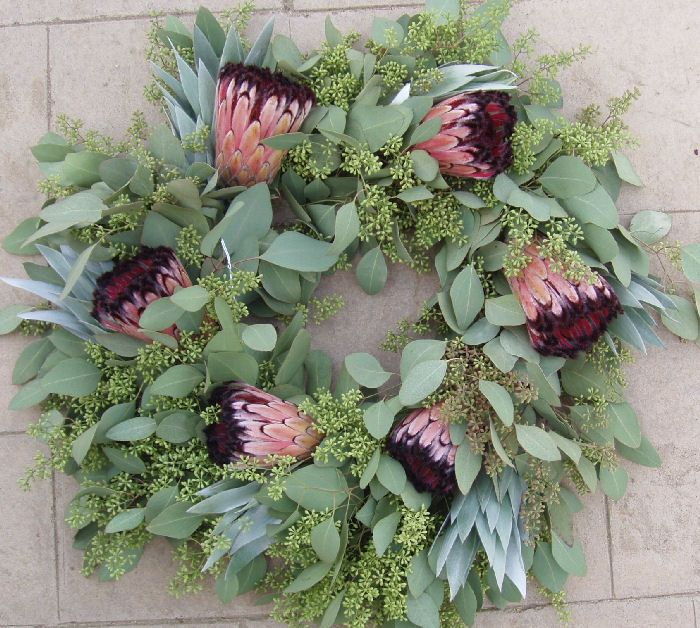 "The silver tree with green seeded eucalyptus makes a nice background to the pink and black mink-type Protea in this wreath. May also use pink ice. Approx. 22"" Wonderful Christmas wreath or advent wreath. $95 + SHIP"
