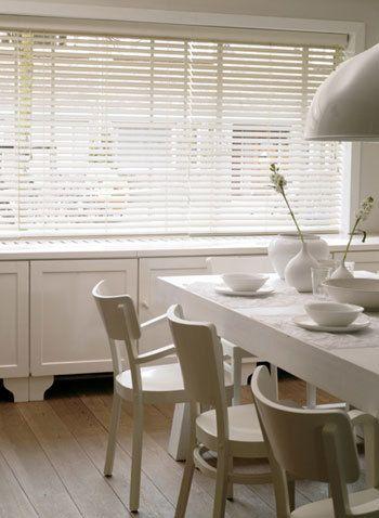 Deze houten jaloezieën (Luxaflex) in een warme wittint vangen het daglicht dat van bovenaf invalt en kaatsen het naar binnen toe.