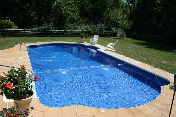 A beautiful stamped concrete deck surrounds this roman end for Swimming pool surrounds design