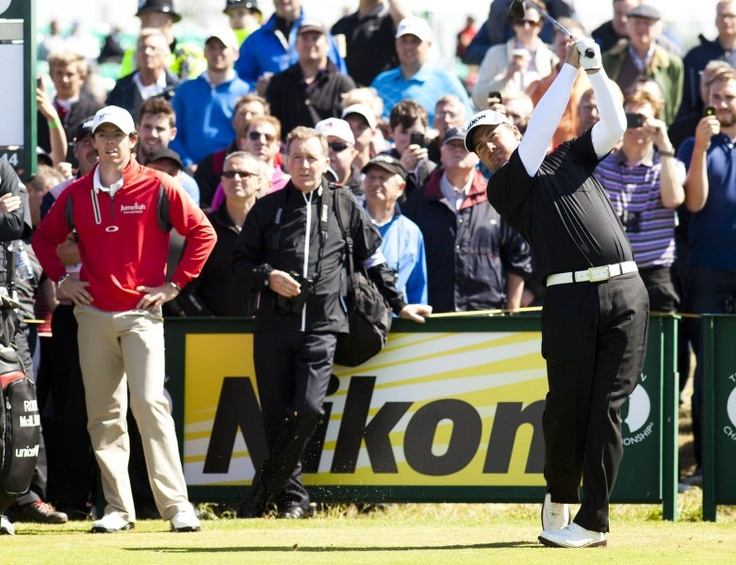 Rory McIllroy watches on as Graham McDowell tees of on the 14th