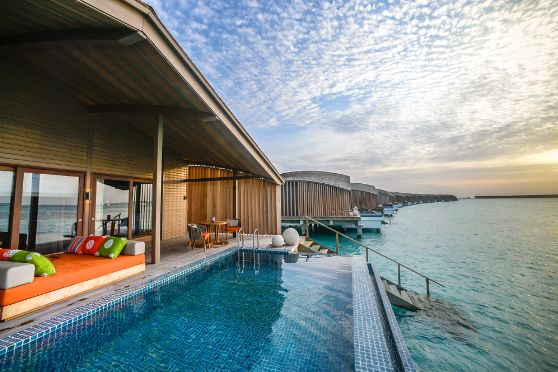 The turquoise ocean stretches beyond the horizon at the Finolhu Villas, where a luxurious private pool sits on stilts above the waters.
