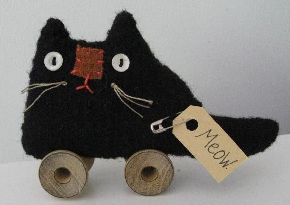 Handstitched from wool. Vintage button eyes, floss whiskers and wooden spool wheels.  Silly kitty!