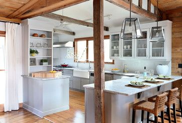 The exposed wood post and beams and the interesting pendants over the peninsula add charm and character to this modern white kitchen.