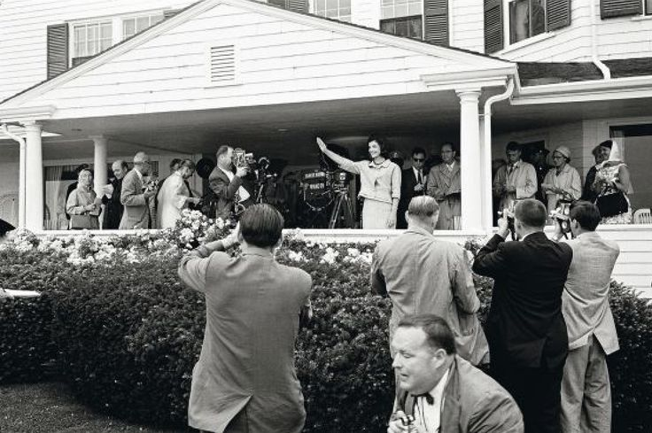 Jacqueline Kennedy waves amongst a horde of photographers shortly after her husband's nomination