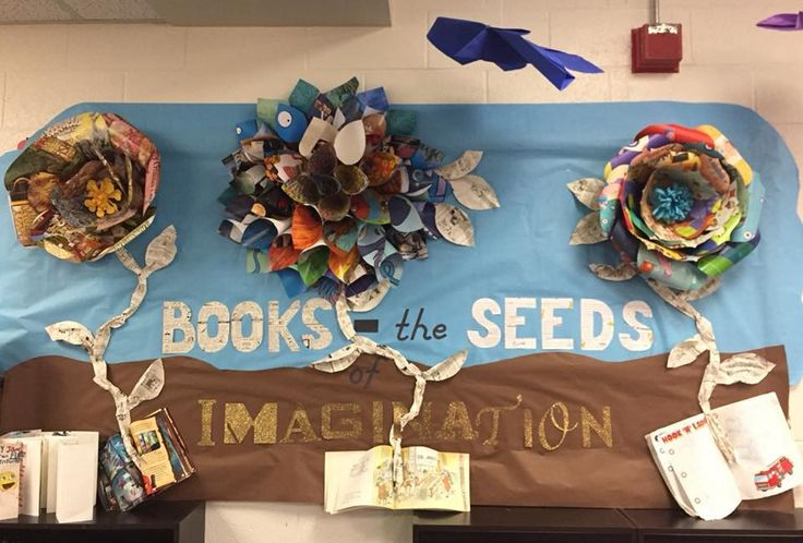 March library bulletin board. Made giant paper flowers with discarded books. Letters and stems with books (imagination is glitter paper saved from previous bulletin board). Finished off by giant hanging origami butterflies (bulletin board paper) in rainbow order created by a team of 5th graders.