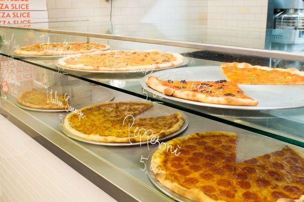 ショーケースには、直径約50センチのホール型ピザが8等分にスライスされて並んでいる。注文すると、焼き直した1切れを紙皿にのせて渡される。500円を「5,00」と5ドルのように表記したり、瓶ビールを紙袋で覆って供するのもNY風
