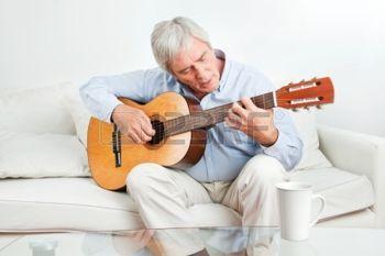 man+en+hobby%3A+Senior+man+thuis+leren+gitaar+spelen