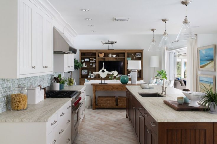 large beach style galley kitchen with an under mount sink, marble countertops, multicolored backsplash, stainless steel appliances, an island, light hardwood floors, recessed panel cabinets, white cabine of Choosing the Perfect Glass Pendant Lights for Well Illuminated Kitchen