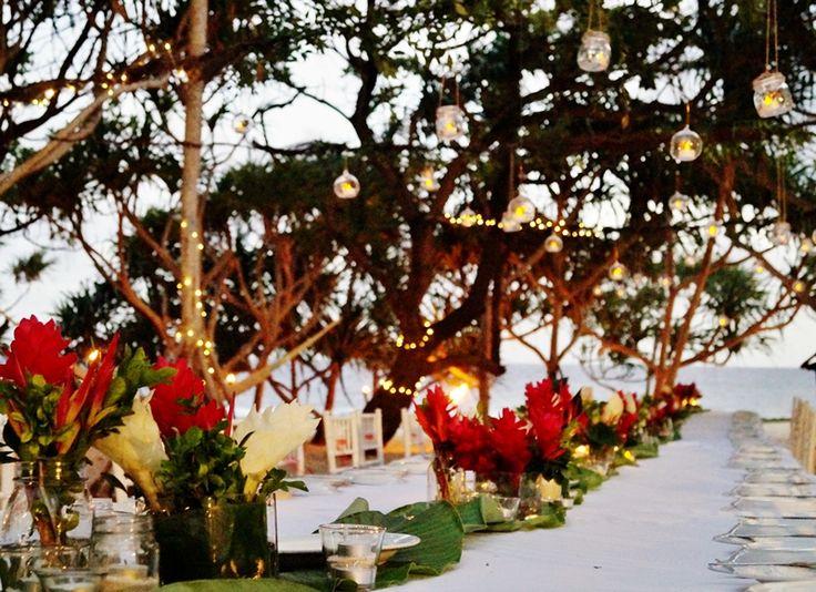 Gorgeous local flowers on the tables and canopy over the table using banyan root, green vines, lots of fairy lights and hanging candles. #vanuatu #VanuatuWeddings #DestinationWedding #IslandWedding #MasonJars #BeachWedding #RehearsalDinner #wedding #PortVila #evrisamting