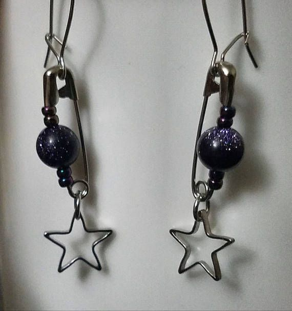 Sparkling blue goldstone beads surround on either side by dark-iris seed beads decorate the silver safety pins on these earrings. Below them hang delicate silver star charms. Proceeds benefit Earth Justice:  www.earthjustice.org  Today's environmental challenges are greater than ever. But we live in a country of strong environmental laws—and Earthjustice holds those who break our nation's laws accountable for their actions.  EARTHJUSTICE HAS BEEN THE LEGAL BACKBONE FOR THOUSANDS OF…