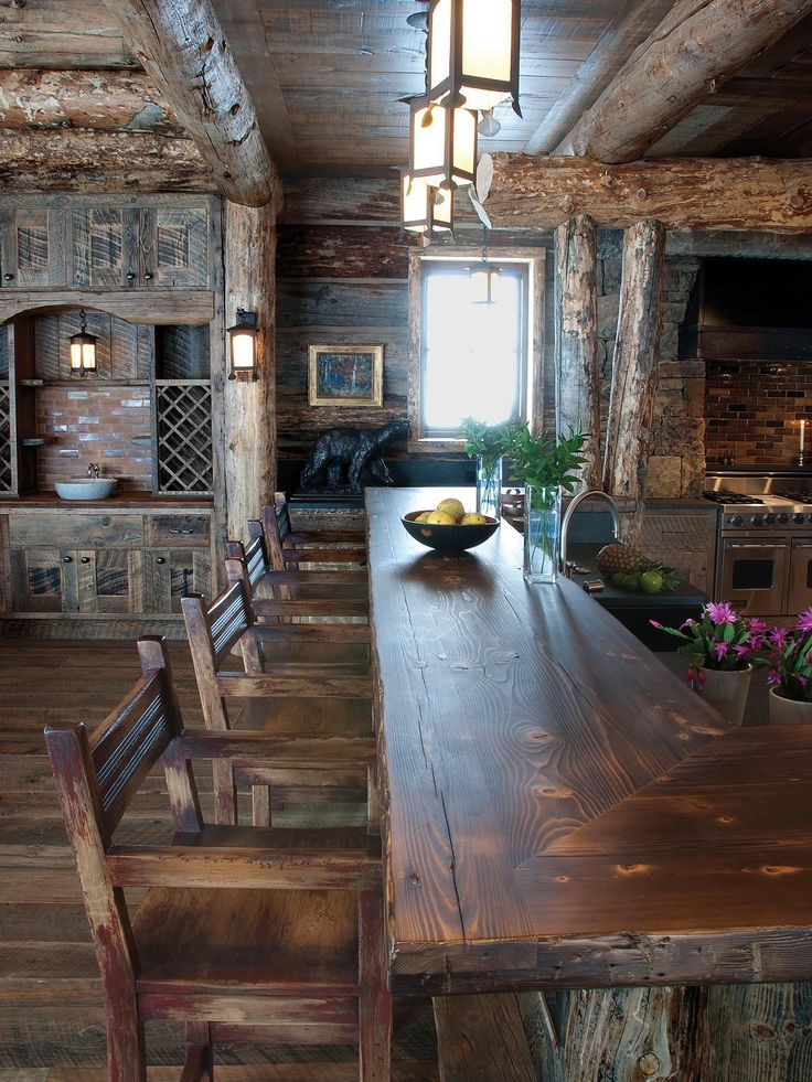 The rustic log cabin is tricked out with elaborate detail in this home that features exposed log ceiling beams and columns and an eating bar made from recycled pine.