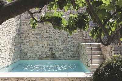 Une piscine entre des murs de pierre