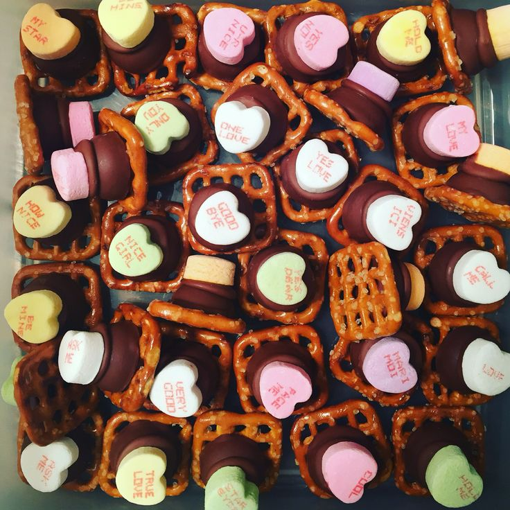 Easy homemade Valentine's Day treats! Pretzels, Hershey kisses and conversation hearts. Preheat oven 275 degrees F, Lay pretzels on baking sheet and top with one Hershey kiss. Place in oven for 4-5 minutes until chocolate is shiny and soft but not melted. Press candy on top and let cool in fridge. Store in sealed container! Yummy!