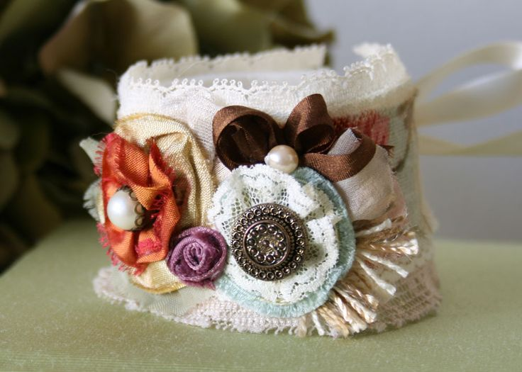 Description For the stylish girl who loves to wear unique accessories, this fabric flower cuff bracelet features layers of hand-cut and sewn textiles in colorful floral patterns and textures with ivor