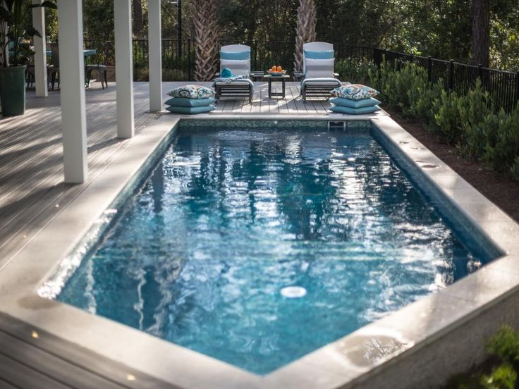 This sunny patio area features a lap pool and eco-friendly chaise lounges made from recycled plastic lumber. Neutral color pillows make the lounge chairs a cozy place for sunning.
