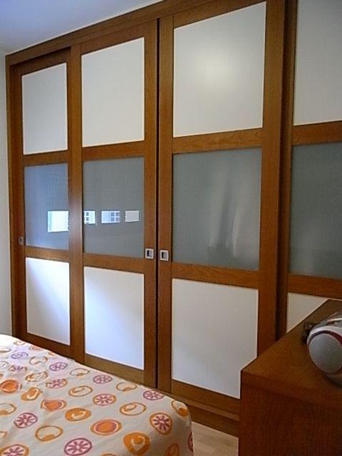 Armario empotrado con puertas correderas. Perfiles de madera de cerezo y plafones lacados y de vidrio.