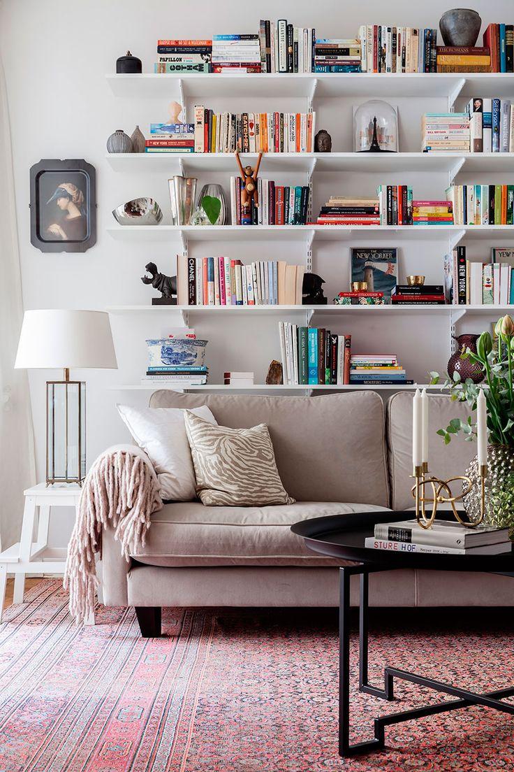 Sala de estar de um apartamento nórdico, decoração clean, paredes branca, mesa de centro preta e sofá claro.