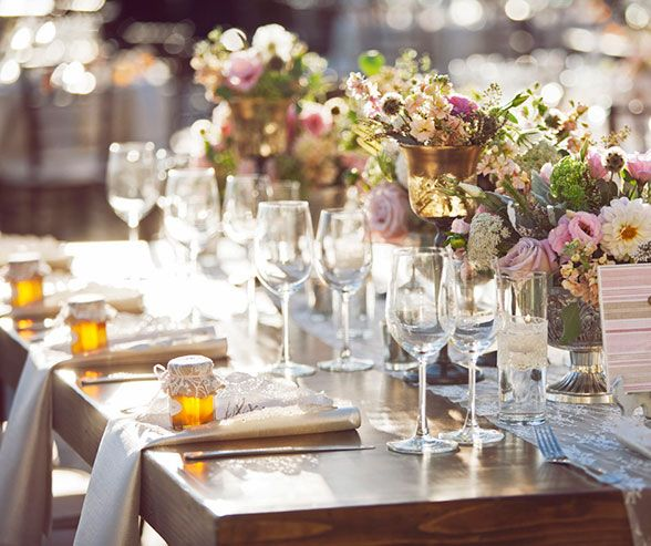 Wooden tables topped with colorful blooms and lace linens are a mix of rustic and vintage charm.