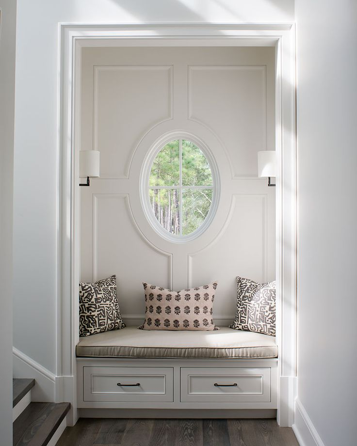 A small sitting nook is tucked below an oval window & matching sconces.