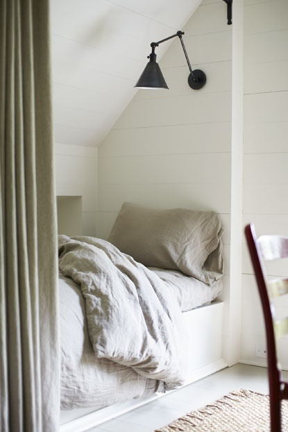 Bed under the eaves, love the draped nook