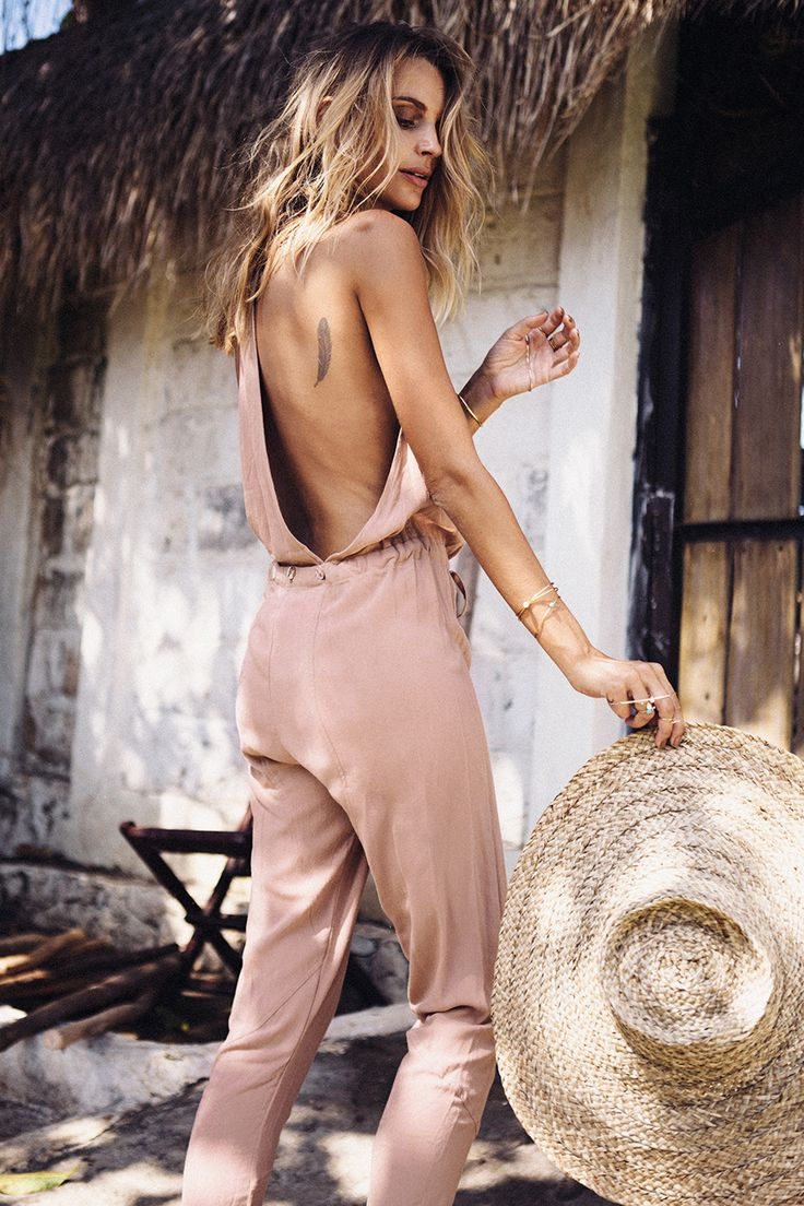The Bronz Jumpsuit is made from crepe-feel fabric in a tan hue and features a halter-style neckline, a cutout Y back and contrast button detailing at the back waist. The adjustable waist-tie can be tied up high at the waist or lower at the hips. Tailored legs, deep arm holes. By Sabo Skirt.