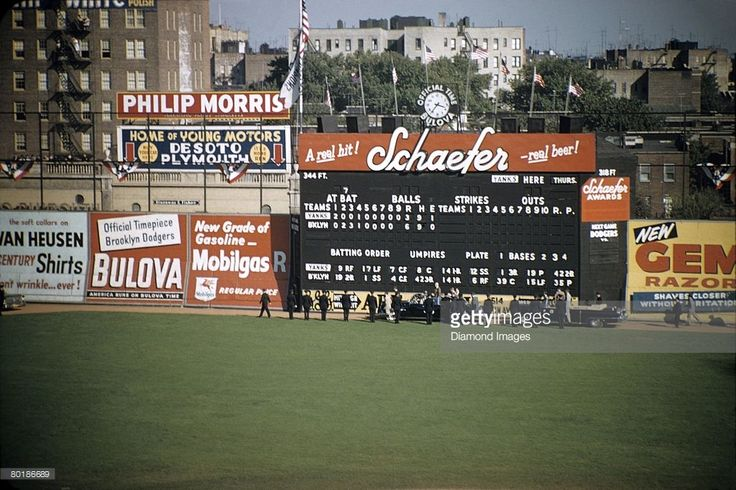 The limousine carrying President Dwight Eisenhower enters Ebbets Field and proceeds along the warning track in front of the main scoreboard prior to game one of the World Series on October 3, 1956 between the New York Yankees and the Brooklyn Dodgers in Brooklyn, New York. 56-01338