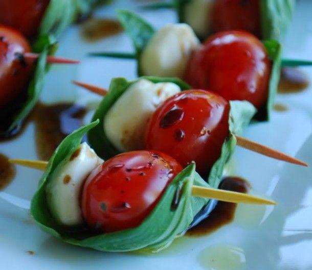Tomaatje, mozzarella en een blad basilicum op een stokje geprikt met wat olijfolie en balsamico erover.