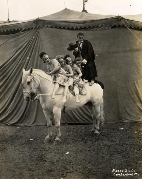 """""""Five circus performers, female and male, sit or stand astride a horse with a tent as a backdrop."""""""