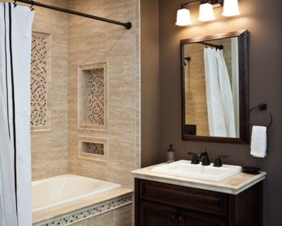 I would add an arched ceiling finished with same mosaics and continue the larger tiles along bottom third of wall behind sink.